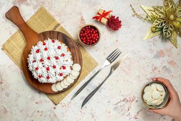 Bovenaanzicht cake met banketbakkersroom op houten bord op krant kerst ornament mes en vork kom met witte chocolade in vrouwelijke hand