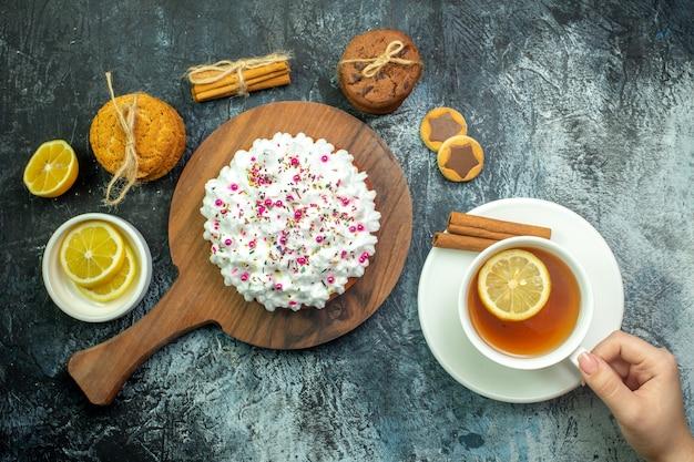 Bovenaanzicht cake met banketbakkersroom op houten serveerplank koekjes kaneelstokjes kopje thee in vrouwelijke hand op grijze tafel