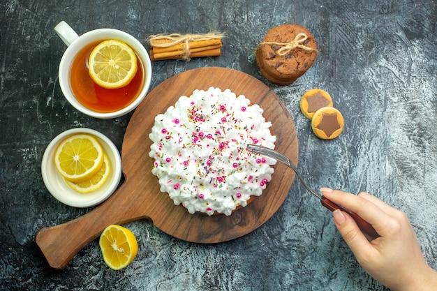 Bovenaanzicht cake met banketbakkersroom op houten serveerplank koekjes kaneelstokjes kopje thee vork in vrouwelijke hand op grijze tafel