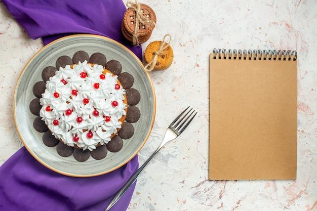 Bovenaanzicht cake met banketbakkersroom op ovale plaat paarse sjaal koekjes vastgebonden met touwvork notebook