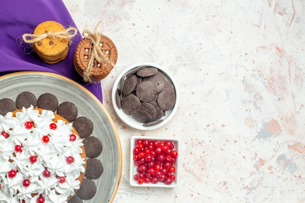 Bovenaanzicht cake met banketbakkersroom op ovale plaat paarse sjaalkoekjes vastgebonden met touwchocolade en bessen in kommen