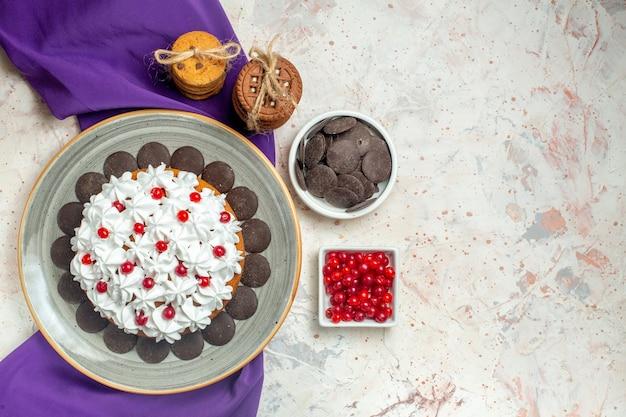 Bovenaanzicht cake met banketbakkersroom op ovale plaat paarse sjaalkoekjes vastgebonden met touwkommen met chocolade en bessen
