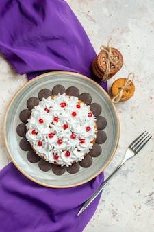 Bovenaanzicht cake met banketbakkersroom op ovale plaat paarse sjaalkoekjes vastgebonden met touwvork op grijze tafel