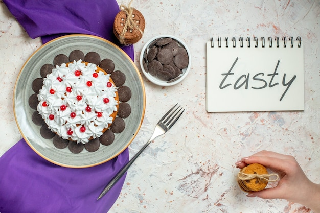 Bovenaanzicht cake met banketbakkersroom op ovale plaat paarse sjaalkoekjes vastgebonden met touwvorkkoekjes in vrouwelijke hand smakelijk geschreven op notitieboekje