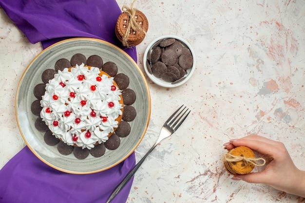Bovenaanzicht cake met banketbakkersroom op ovale plaat paarse sjaalkoekjes vastgebonden met touwvorkkoekjes in vrouwelijke hand