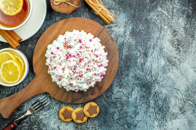 Bovenaanzicht cake met banketbakkersroom op snijplank kopje thee op smaak gebracht door citroen en kaneelkoekjesvork op grijze achtergrond