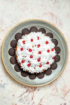 Bovenaanzicht cake met chocolade en witte banketbakkersroom op ovale plaat