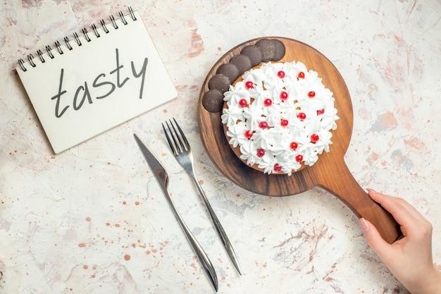 Bovenaanzicht cake met chocolade en witte banketbakkersroom op snijplank in vrouwelijke hand. lekker geschreven op notebook