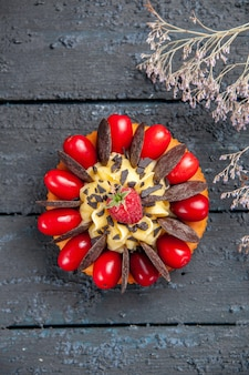 Bovenaanzicht cake met cornel fruit en chocolade op donkere houten ondergrond