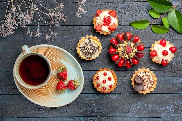 Bovenaanzicht cake met cornel fruit framboos en chocolade omgeven met taartjes bladeren en een kopje thee op donkere houten tafel