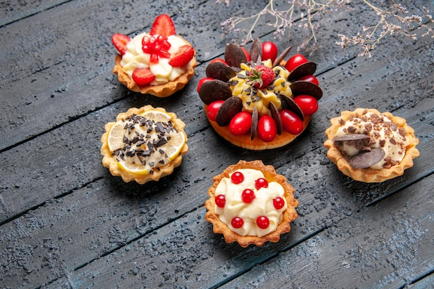 Bovenaanzicht cake met cornel fruit framboos en chocolade omgeven met taartjes op een donkere ondergrond