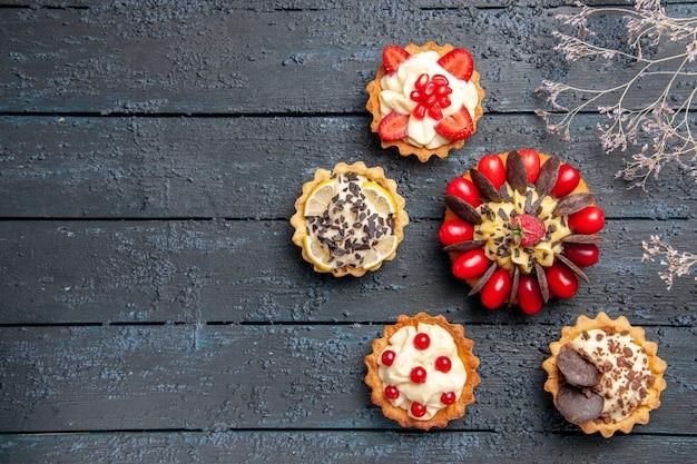 Bovenaanzicht cake met cornel fruit framboos en ronde chocolade aan de rechterkant van donkere ondergrond