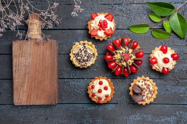Bovenaanzicht cake met cornel fruit frambozen en chocoladetaartjes bladeren en een snijplank op donkere ondergrond