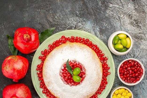 Bovenaanzicht cake met granaatappel drie granaatappelkommen met bessen en een bord cake