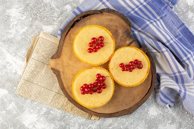 Bovenaanzicht cake met veenbessen lekker gebakken op het houten bureau en grijze achtergrond cake suiker zoete bak