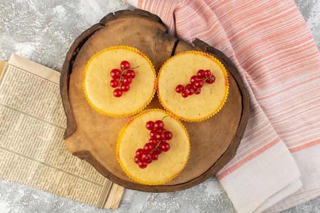 Bovenaanzicht cake met veenbessen lekker gebakken op het houten bureau en grijze achtergrond suiker zoete bak