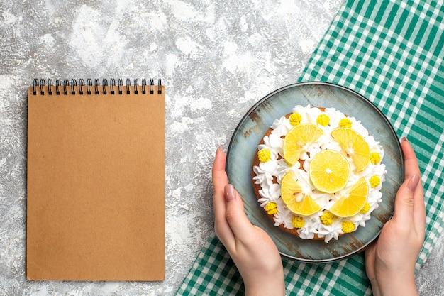 Bovenaanzicht cake met witte banketbakkersroom en schijfjes citroen op cyaan plaat op groen en wit geruit tafelkleed