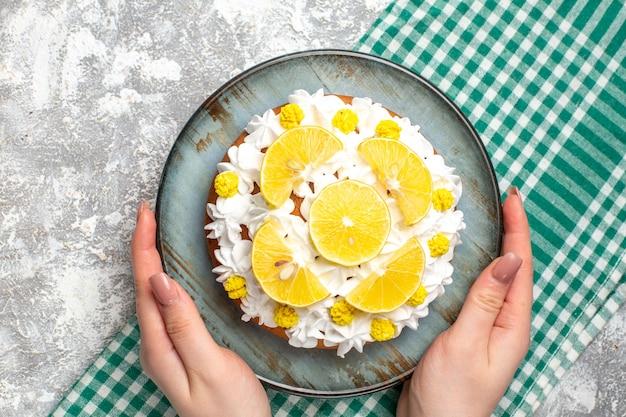 Bovenaanzicht cake met witte banketbakkersroom en schijfjes citroen op ronde plaat in de hand van de vrouw