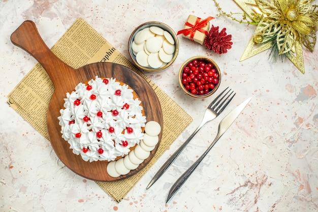 Bovenaanzicht cake met witte banketbakkersroom op een houten bord op krant. kerst ornament