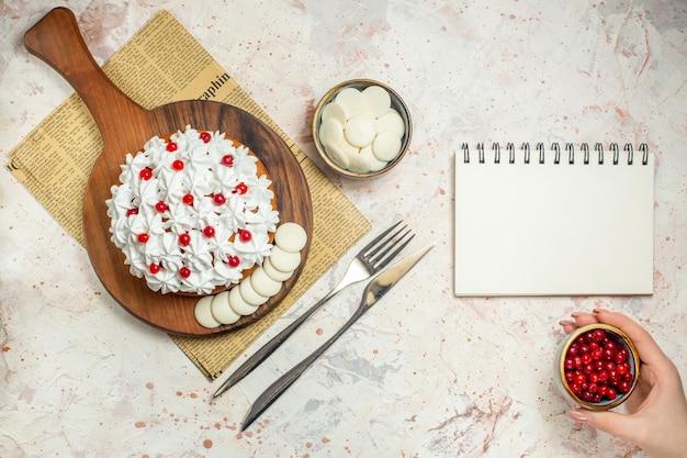 Bovenaanzicht cake met witte banketbakkersroom op een houten bord op krant. kom met bessen in de hand van de vrouw. leeg notitieboekje