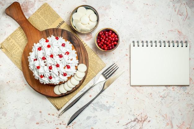 Bovenaanzicht cake met witte banketbakkersroom op een houten bord op krant. leeg notitieboekje