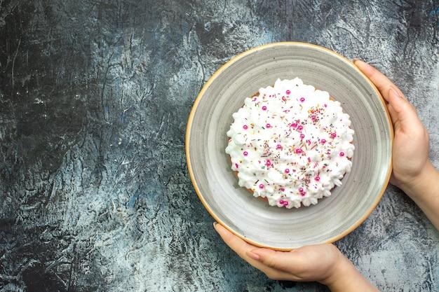 Bovenaanzicht cake met witte banketbakkersroom op grijze ronde schotel in vrouwelijke hand op grijze tafel met vrije ruimte