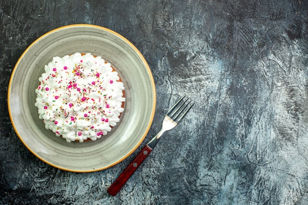Bovenaanzicht cake met witte banketbakkersroom op grijze ronde schotelvork op grijze tafel met kopieerplaats
