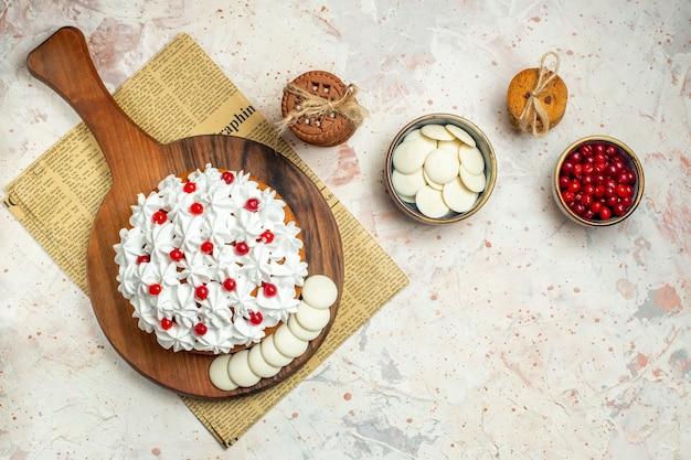 Bovenaanzicht cake met witte banketbakkersroom op houten bord op krant