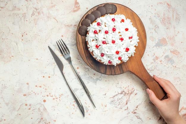 Bovenaanzicht cake met witte banketbakkersroom op houten snijplank in vrouwelijke hand