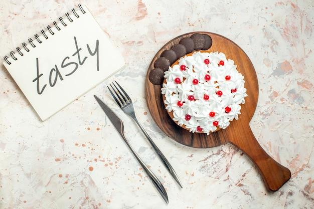 Bovenaanzicht cake met witte banketbakkersroom op houten snijplank