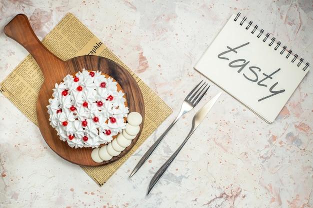 Bovenaanzicht cake met witte banketbakkersroom op snijplank. lekker geschreven op notebook Gratis Foto