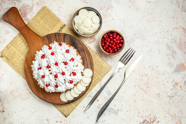 Bovenaanzicht cake met witte banketbakkersroom op snijplank op krantenvork en diner mes kommen met witte chocolade en bessen op lichtgrijze tafel