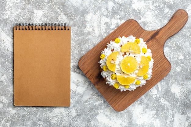 Bovenaanzicht cake met witte room en schijfjes citroen op snijplank en leeg notitieboekje