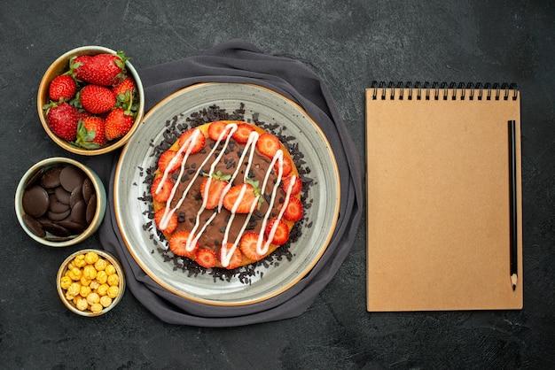Bovenaanzicht cake op tafelkleed kommen van hazelnoot aardbei en chocolade en cake met stukjes chocolade en aardbei naast crème notitieboekje met zwart potlood op grijs tafelkleed op zwarte tafel