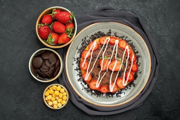 Bovenaanzicht cake op tafelkleed smakelijke cake met chocolade en aardbei en kommen aardbei hazelnoot en chocolade op grijs tafelkleed op zwarte tafel