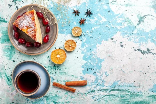 Bovenaanzicht cakeplak wit verse rode kornoeljes en kopje thee op blauwe achtergrond fruitcake bakken taart koekje zoet