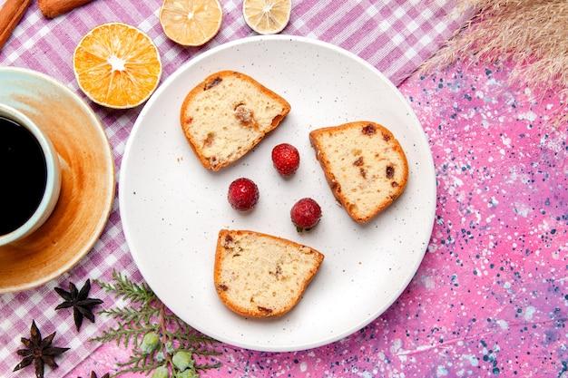 Bovenaanzicht cakeplakken met aardbeien en koffie op roze bureaucake bak zoet koekje suiker kleur taartkoekje