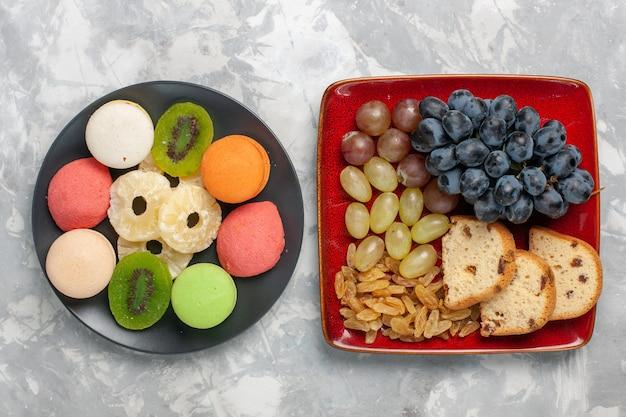 Bovenaanzicht cakeplakken met druiven en kleine cakes op witte ondergrond