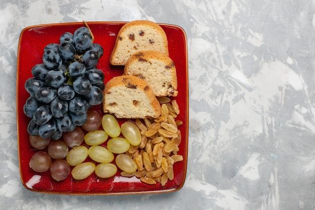 Bovenaanzicht cakeplakken met druiven en rozijnen in rode plaat op wit bureau