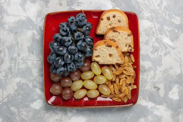 Bovenaanzicht cakeplakken met druiven en rozijnen in rode plaat op witte ondergrond