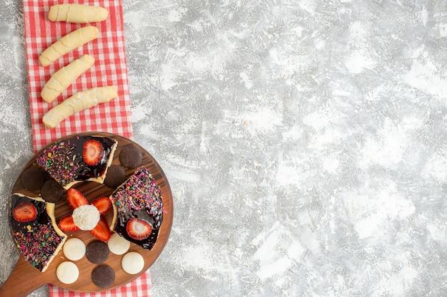 Bovenaanzicht cakeplakken met koekjes en snoep op witte ondergrond