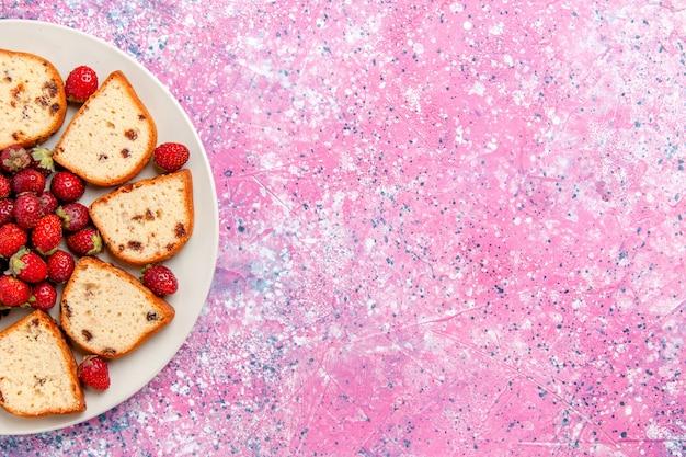 Bovenaanzicht cakeplakken met rozijnen binnen plaat met verse aardbeien op lichtroze bureaucake bak zoete biscuit kleur taart suikerkoekjes