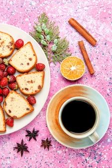 Bovenaanzicht cakeplakken met verse aardbeien en koffie op roze bureaucake bak zoet koekje kleur taart suiker koekje