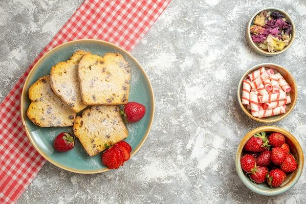 Bovenaanzicht cakeplakken met verse aardbeien en snoepjes op lichte oppervlaktetaartvruchten