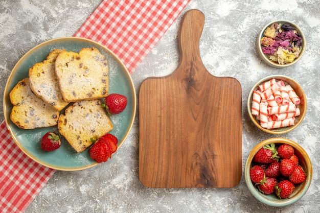 Bovenaanzicht cakeplakken met verse aardbeien op lichte oppervlakte zoete taart fruit