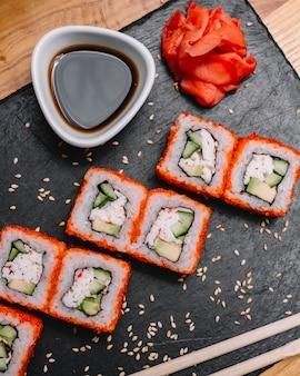 Bovenaanzicht californië roll krab vlees komkommer tobiko kaviaar gember en sojasaus op een bord
