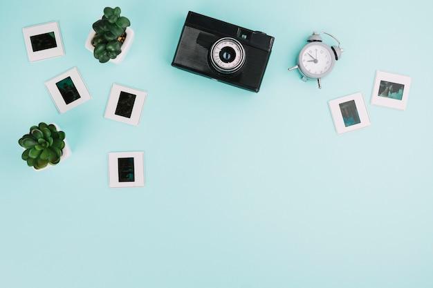 Bovenaanzicht camera met negatieven, klok en planten