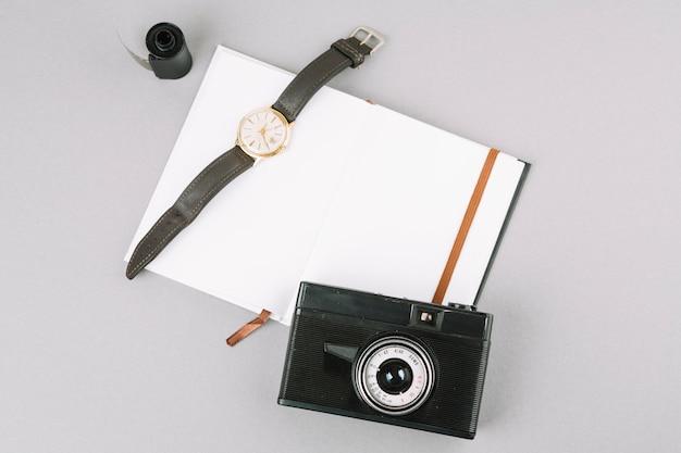 Bovenaanzicht camera met notebook en horloge