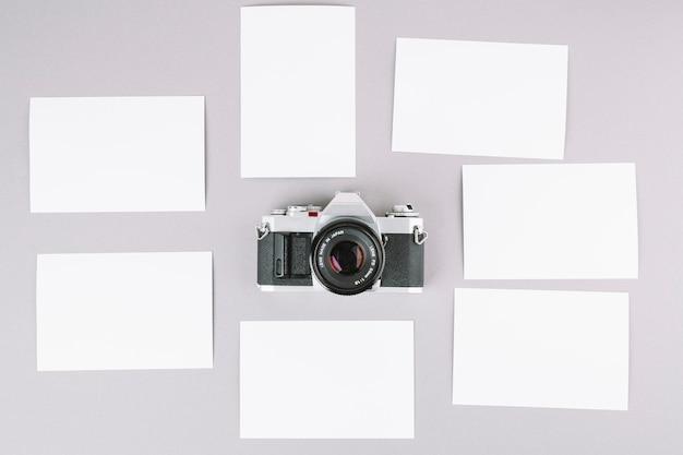 Bovenaanzicht camera omringd door papieren