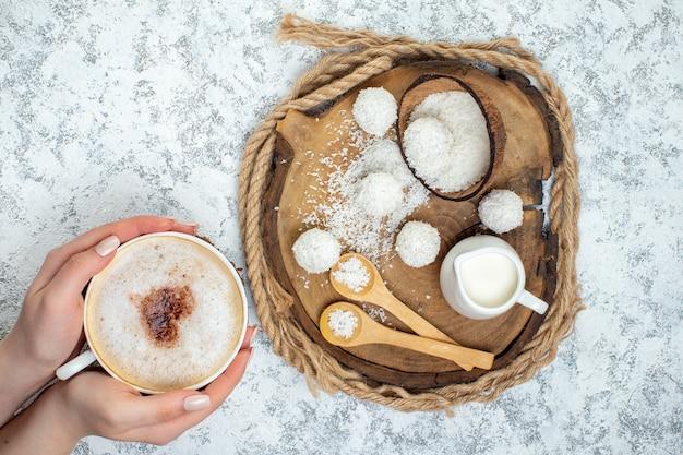 Bovenaanzicht cappuccino-kop in vrouwelijke hand kokosballen melkkom lepels op houten bord op grijze ondergrond